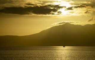 A small fishing boat with Arran behind and the sun setting.